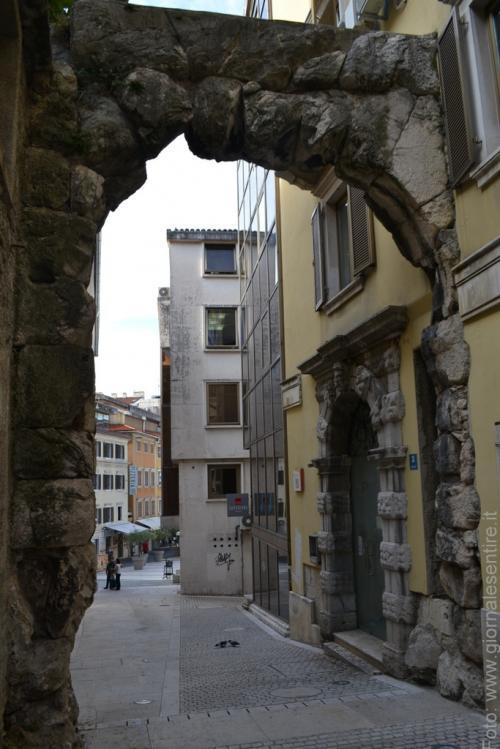 L'arco romano in un continuo contrasto tra passato e presente - foto C.Perer