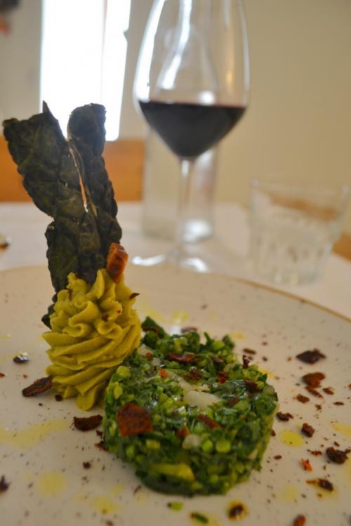 Una chips di foglia di cavolo nero su un puré di piselli secchi e un trito delizioso di erbe di campo spruzzate da peperone essicato e accompagnato da un ottimo Nero di Troia